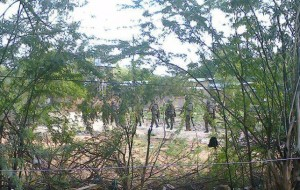 Kenya Defence Forces soldiers move behind a thicket in Garissa town in this photograph taken with a mobile phone