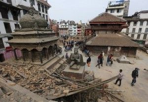 People walk past the rubble of a temple destroyed in Saturday's earthquake, in Kathmandu