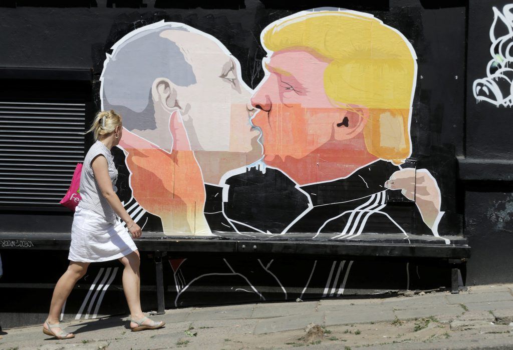 A woman walks past a graffiti depicting U.S. Republican presidential candidate Donald Trump (R) and Russia's President Vladimir Putin in Vilnius, Lithuania, June 1, 2016. REUTERS/Ints Kalnins  FOR EDITORIAL USE ONLY. NO RESALES. NO ARCHIVES